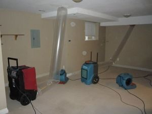 Water Damage Restoration Equipment Being Used In A Basement